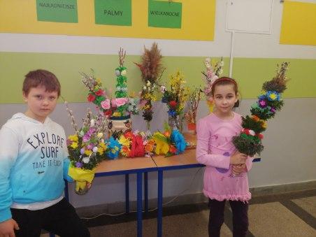 Szymon i Marietta prezentują na tle innych prac swoje palmy, które wykonali z gałązek wierzbowych ozdobionych papierowymi kwiatami.