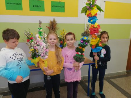 Od lewej strony stoją Szymon, Maja, Marietta i Basia. Dzieci prezentują swoje prace. Maja dumnie pokazuje swoją palmę ozdobioną różami i piórkami. Basia mocno trzyma swoją ogromną palmę wykonaną wraz z rodzicami. Palma ozdobiona bibułą oraz kolorową krepiną zdobyła I miejsce.
